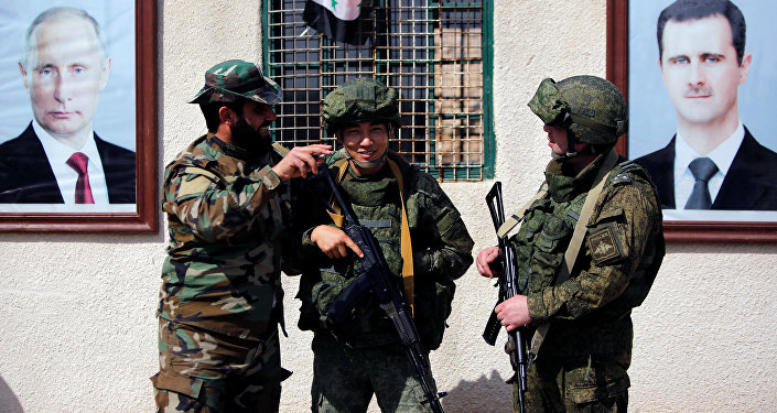 Syrian and Russian soldiers are seen at a checkpoint near Wafideen camp in Damascus, Syria March 2, 2018
