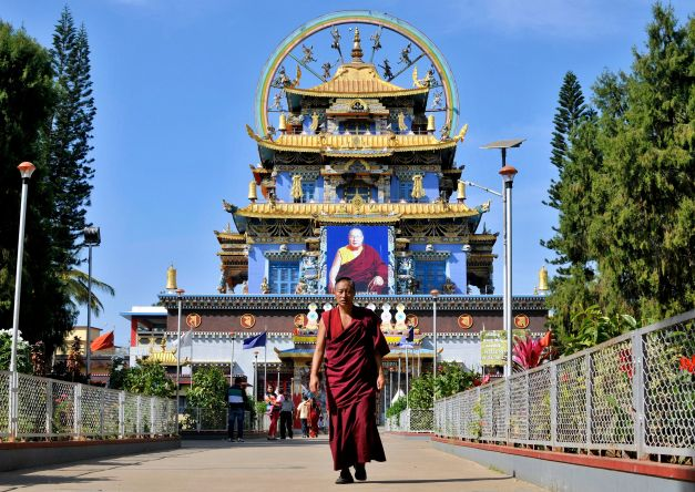 A Tibetan Buddhist monk walks in front of the Golden Temple inside the Nyingmapa Monastery in Bylakuppe, southwest of Bengaluru, previously known as Bangalore, December 4, 2014. The settlement came up on land set aside for refugees after Tibet's Dalai Lama fled into exile in India in 1959. While the spiritual leader stays in the hill resort of Dharamsala in northern India, an estimated 20,000 Tibetans live in Bylakuppe. Picture taken December 4, 2014. REUTERS/Abhishek N. Chinnappa (INDIA - Tags: RELIGION TRAVEL) - RTR4JV3C