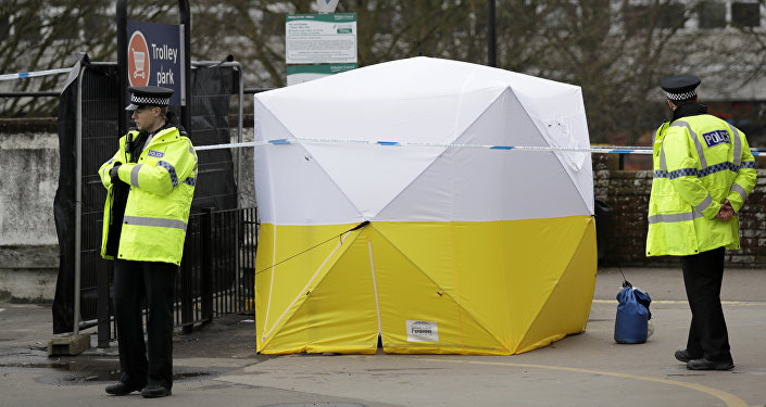 Police officers guard a cordon around a police tent covering a supermarket car park pay machine near the area where former Russian double agent Sergei Skripal and his daughter were found critically ill following exposure to the Russian-developed nerve agent Novichok in Salisbury, England, Tuesday, March 13, 2018