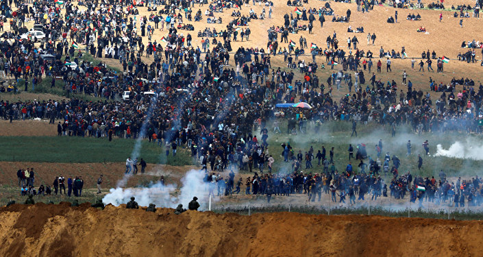 Israeli soldiers shoot tear gas from the Israeli side of the Israel-Gaza border, as Palestinians protest on the Gaza side of the border, March 30, 2018