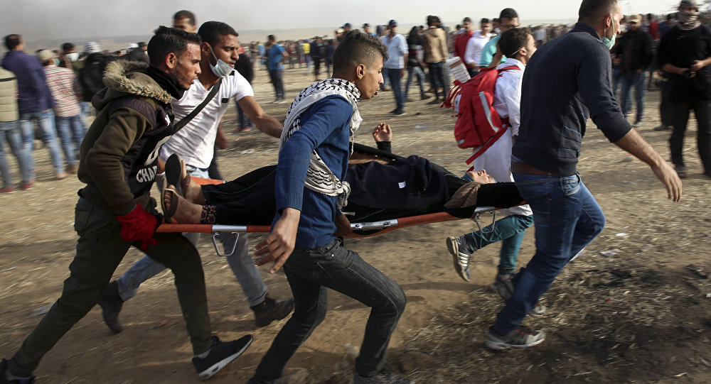Palestinian protesters evacuate a wounded woman during clashes with Israeli troops along Gaza's border with Israel, Friday, April 13, 2018.