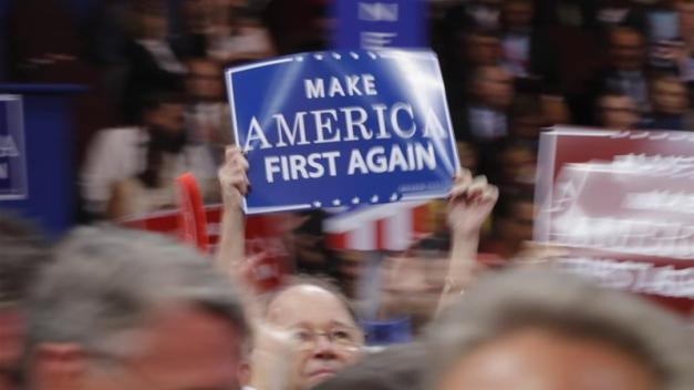 "A delegate waves a ""Make America First Again"" sign on the floor during the Republican National Convention in Cleveland, Ohio, US [Brian Snyder/Reuters]"