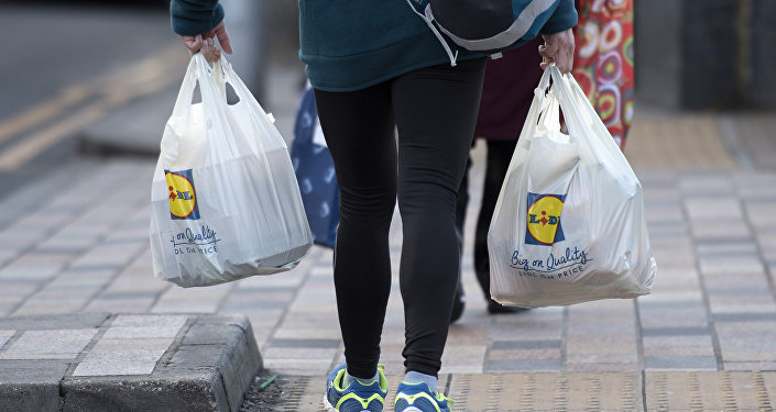 A person leaves with their goods in plastic carrier bags after shopping at a branch of Lidl in south London on January 10, 2018