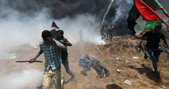 Palestinian demonstrators run for cover during a protest against U.S. embassy move to Jerusalem and ahead of the 70th anniversary of Nakba, at the Israel-Gaza border in the southern Gaza Strip May 14, 2018