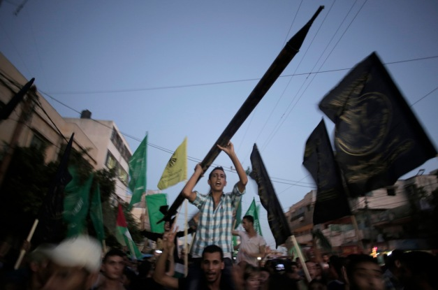 A man holds a mock Qassam rocket as Palestinians celebrate a 2014 cease-fire in Gaza City, Aug. 26, 2014. Khalil Hamra | AP