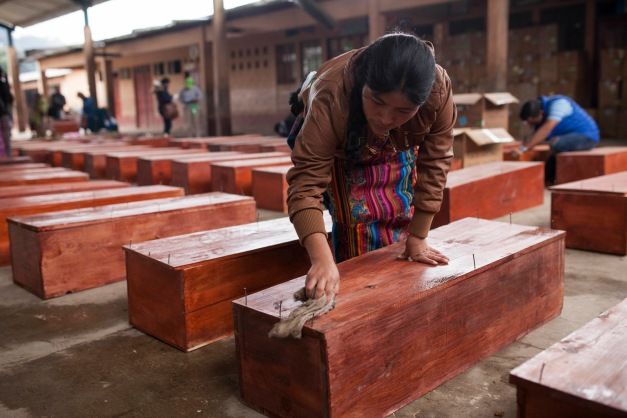 An Ixil Mayan woman cleans a coffin holding the remains of a civil war victim prior to a mass burial in Santa Avelina, Guatemala, Nov. 30, 2017. After seven years of work by forensic anthropologists, including DNA tests to locate relatives, the remains of 172 indigenous Ixil Mayans killed during the civil war between 1978 and 1982 were buried in the western mountains of Guatemala. (AP/Moises Castillo)