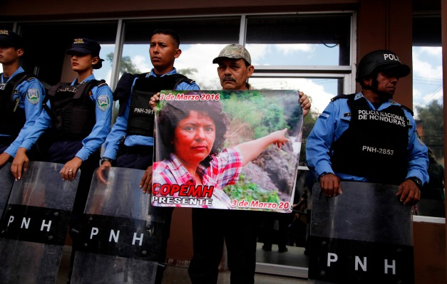A man, flanked by police, holds a placard showing an image of slain environmental activist and Goldman Environmental Prize winner Berta Caceres, as part of a protest demanding justice for her murder, outside the Prosector's Office in Tegucigalpa, Honduras, March 2, 2018. (AP/Fernando Antonio)