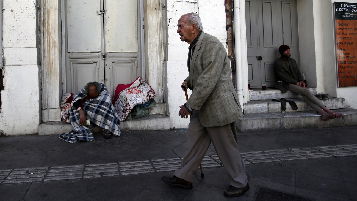An elderly man passes by homeless men in Athens, April 23, 2018. Thanassis Stavrakis | AP