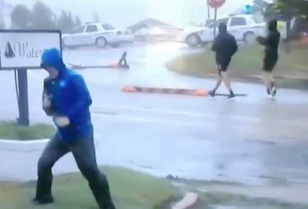 Image: Hilarious fake news: Weather Channel reporter fakes hurricane-force winds while two guys casually stroll down the street behind him, wearing shorts