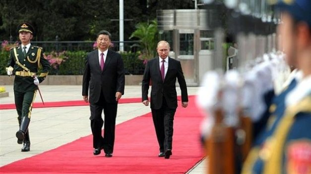 Russia's President Vladimir Putin (center R) reviews a military honor guard with Chinese President Xi Jinping (center L) during a welcoming ceremony outside the Great Hall of the People in Beijing on June 8, 2018.