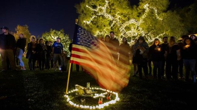 People stand around candles in the grass next to a US flag during a vigil to pay tribute to the victims of a shooting in Thousand Oaks, California, on November 8, 2018. (Photo by AFP)