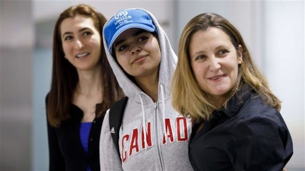 Asylum seeker Rahaf Mohammed al-Qunun (C), 18, smiles as she is introduced to the media at Toronto Pearson International Airport, alongside Canadian Minister of Foreign Affairs Chrystia Freeland (R), in Toronto, Canada, on January 12, 2019. (Photo by AFP)