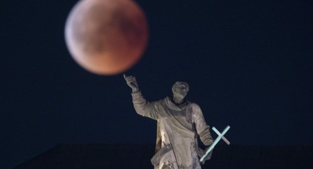 The full moon appears behind the Mattielli-statue on the Hofkirche church during a blood moon eclipse over Dresden, eastern Germany, on July 27, 2018