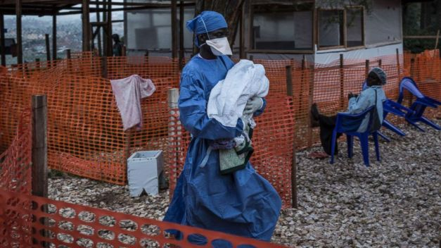 A caretaker already cured of Ebola is seen carrying a four day old baby suspected of having Ebola into a Medecins Sans Frontieres supported Ebola treatment center in Butembo, Congo, Nov. 4, 2018.