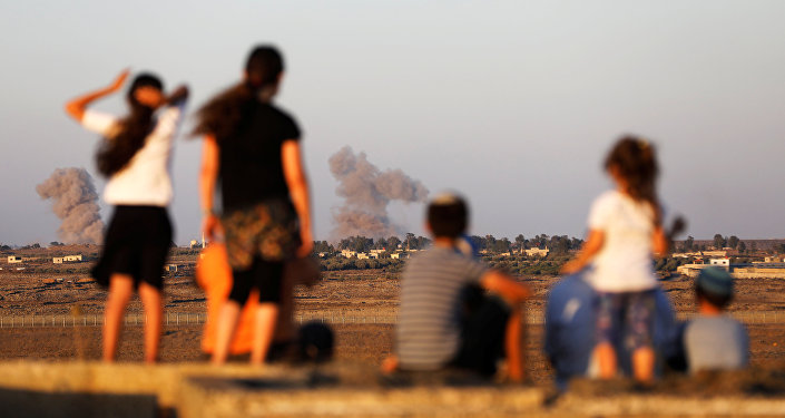 Israeli kids look over the Israeli Syrian border as smoke can be seen following an explosion at its Syrian side it is seen from the Israeli-occupied Golan Heights, Israel July 23, 2018