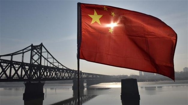 The Chinese flag flies on the Yalu River Broken Bridge, with the Sino-Korean Friendship Bridge, and the North Korean city of Sinuiju behind, in the border city of Dandong, in China's northeast Liaoning province on February 23, 2019. (Photo by AFP)