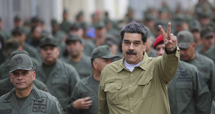 In this handout photo released by the Miraflores Presidential Press Office, Venezuela's President Nicolas Maduro flashes a V for Victory hand gesture after arriving at the Fort Tiuna military base in Caracas, Venezuela, Wednesday, Jan. 30, 2019.