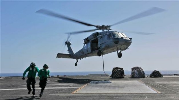 "This handout picture released by the US Navy on May 10, 2019 shows naval logistics specialists attaching cargo to an MH-60S Sea Hawk helicopter from the ""Nightdippers"" of Helicopter Sea Combat Squadron (HSC) 5 from the flight deck of the Nimitz-class aircraft carrier USS Abraham Lincoln (CVN 72)."