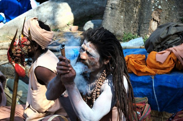 An ascetic devotee of Lord Shiva smokes ganja from a traditional clay <em>chillum</em>.