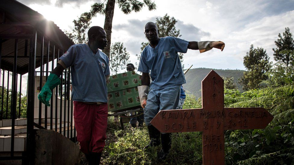 Health workers carry a coffin containing a victim of the Ebola virus