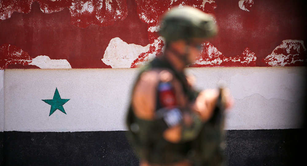 A Russian soldier stands guard near a Syrian national flag