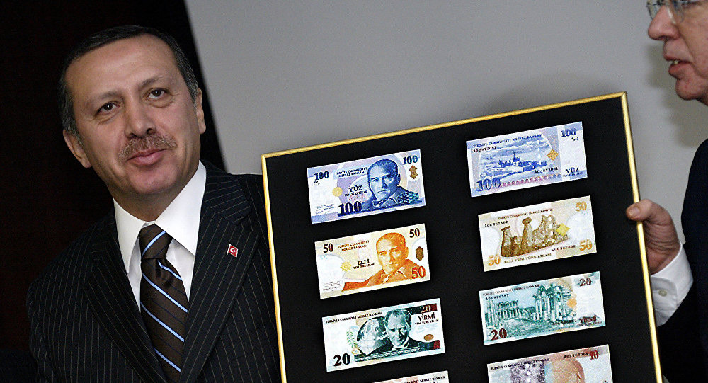 Recep Tayyip Erdogan holds a board featuring the new Turkish lira samples (File)