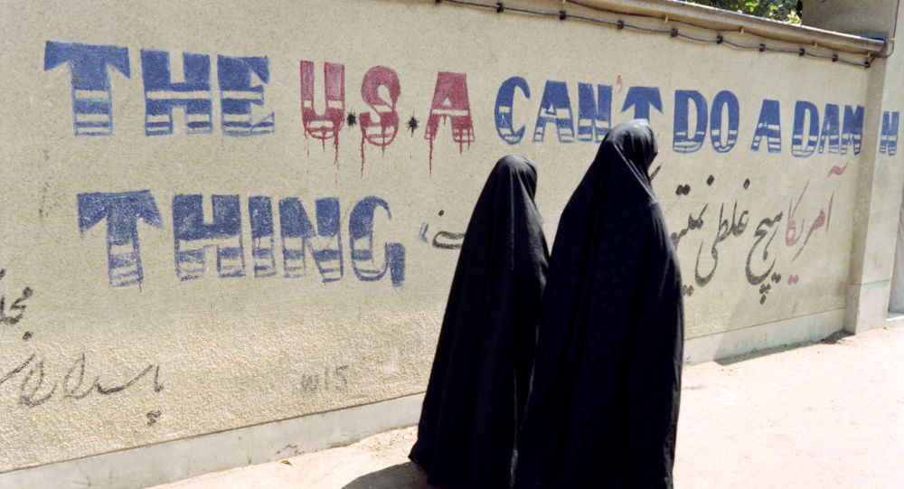 Two Iranian women wearing chadors walk past an anti-American slogan in a street of the Djarmaran district where lived Ayatollah Khomeini on July 30, 1989