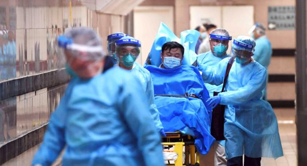Medical staff transfer a patient of a highly suspected case of a new coronavirus at the Queen Elizabeth Hospital in Hong Kong, China January 22, 2020.